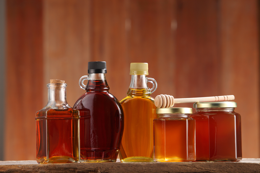 Variety of maple syrup and honey jars with honey dipper