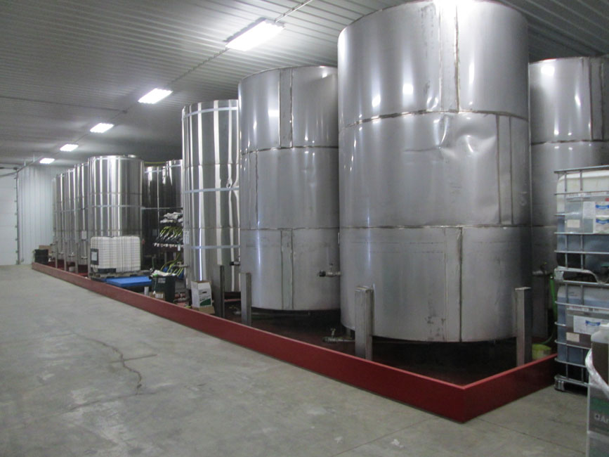 Photo shows stainless steel bulk liquid pesticide storage tanks in a metal containment dike.