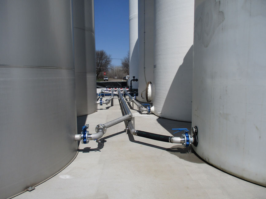 Photo shows pluming running from the main valves on bulk liquid fertilizer tanks.