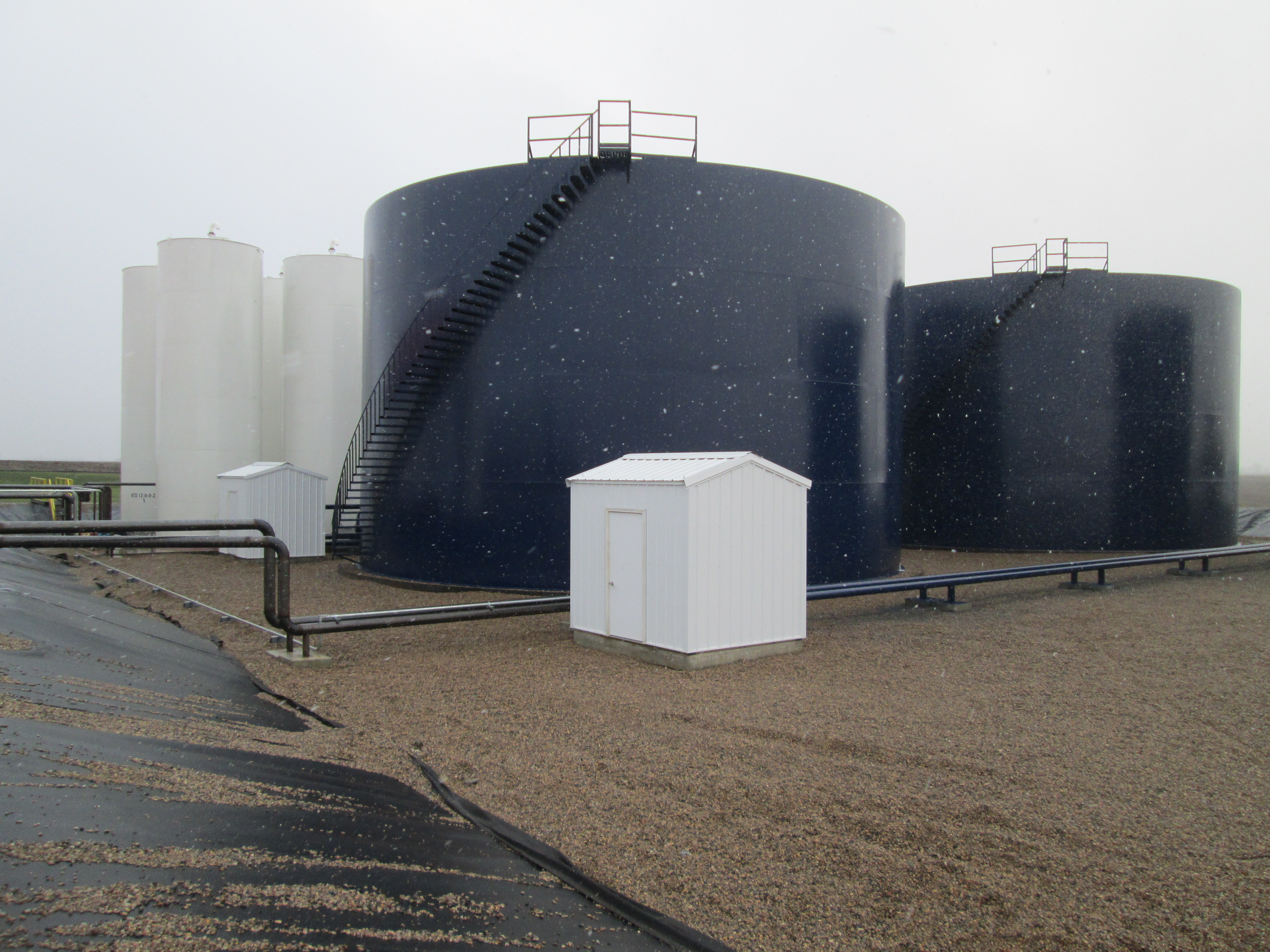 Photo shows field erected and manufactured fertilizer tanks located in an outdoor fertilizer containment dike.