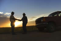 Farmers shaking hands near a truck at sunset